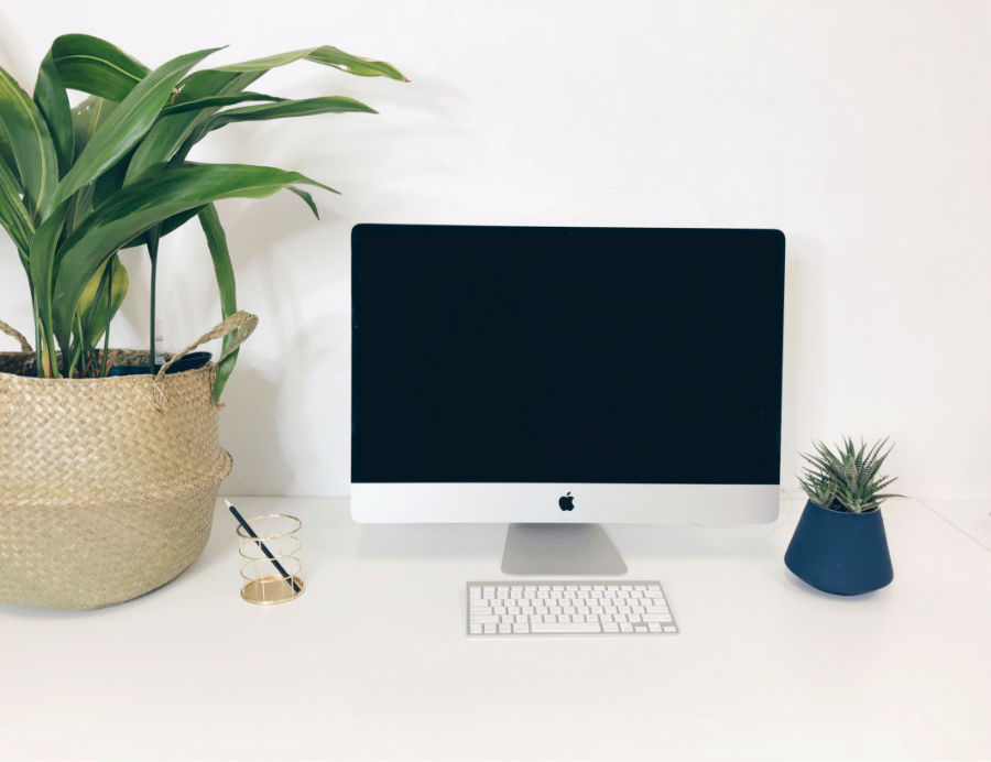 desk with Apple Mac desktop with plants next to computer